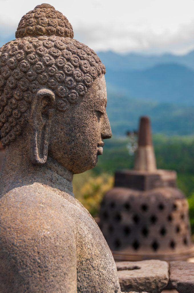 Sitting stone Buddha in front of Stupa at borobudur