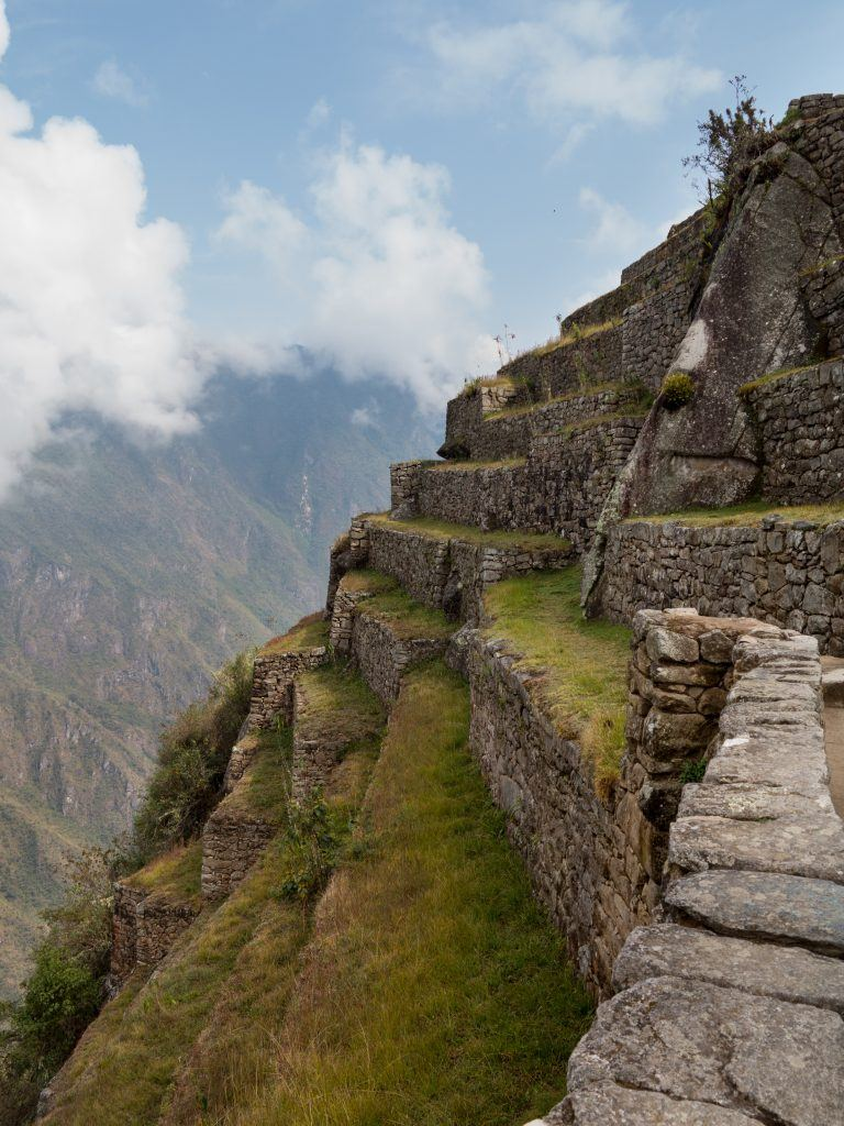 Morning views of Machu Picchu as mist clears from the mountainside with terraces