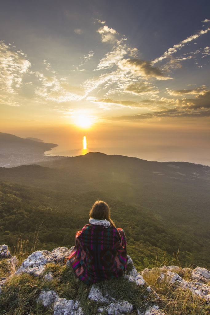 sitting girl in yellow sunrise in mountains above sea
