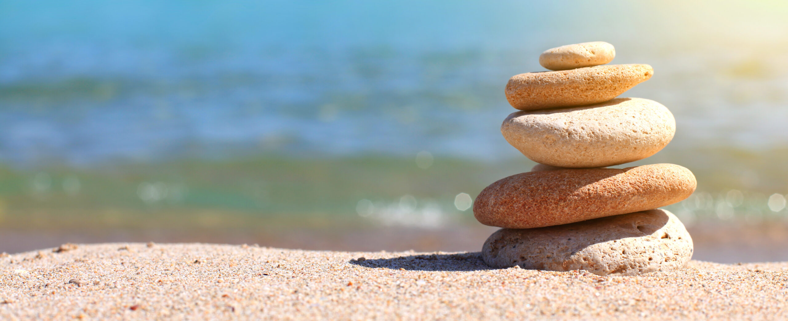 Stack of stones on sand and sea. Horizontal nature background.